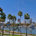 Image of Long Beach CA showing the building skyline palm trees and the Long Beach Harbor