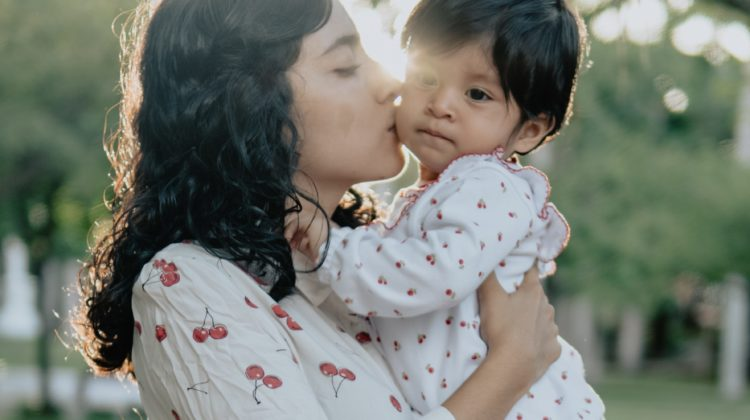 image of young woman with dark hair wearing a white blouse with cherries on it. She is holding and kissing a small baby